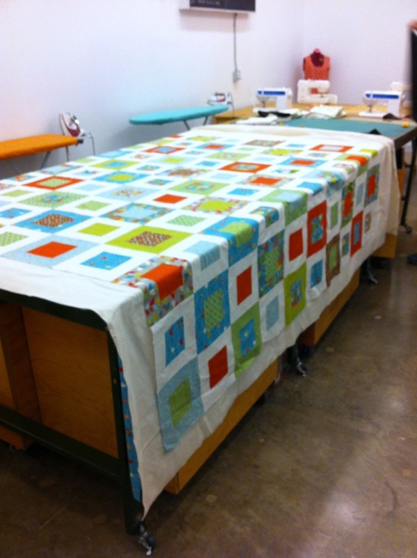 pinning bed quilt at spool of thread