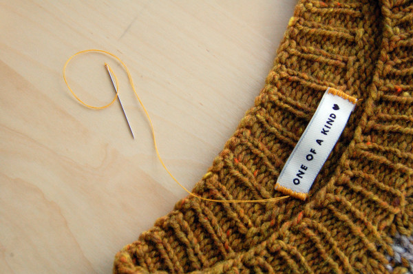 sewing labels into handknit sweaters 1